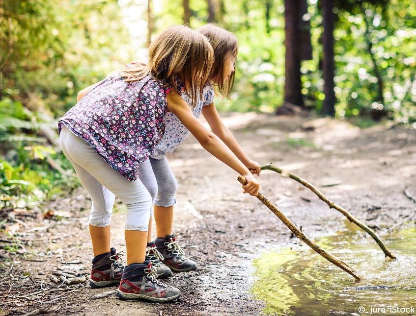 AUBEL_petites filles jouant avec un bois dans l'eau©_jureistock2020